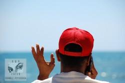 Reisefotografie, Porträtfotografie, Strand, Mann mit roter Cap und Handy, Schmelz Fotodesign